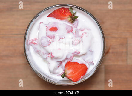 Melted vanilla ice cream with strawberry slices - Stock Photo