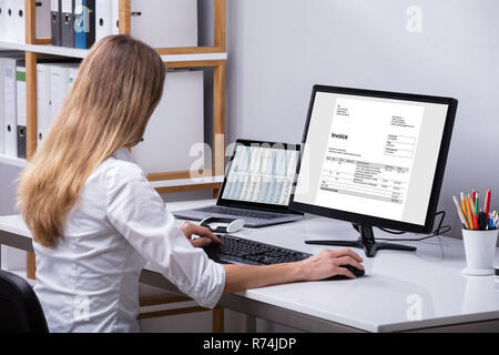 Businesswoman Checking Invoice On Computer - Stock Photo