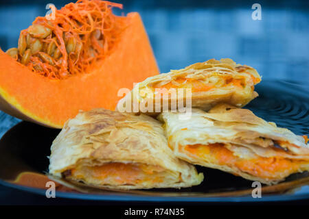Traditional homemade dessert, roasted pumpkin strudel or pie made with light puff pastry sheet and grated pumpkin - Stock Photo
