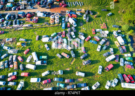 Car wrecks on meadow aerial view - Stock Photo