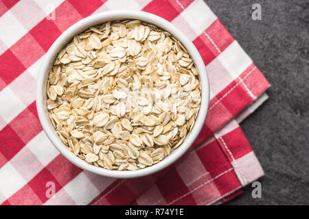 Dry rolled oatmeal in bowl - Stock Photo