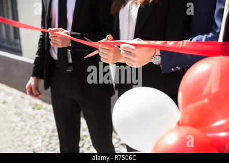 Businesspeople Hand Cutting Red Ribbon - Stock Photo