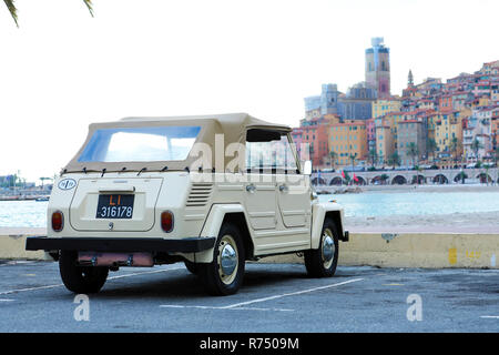 Menton, France - December 7, 2018:  Beautiful Vintage Volkswagen Thing 1973 (Rear View) Car On The Beach With Colorful Houses Of Menton Old Town In Th - Stock Photo