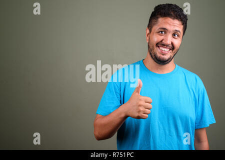 Bearded Persian man wearing blue shirt against colored backgroun - Stock Photo