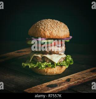 cheeseburger in a bun with sesame seeds - Stock Photo