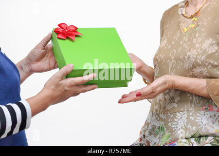 Elderly woman receiving a gift from daughter - Stock Photo