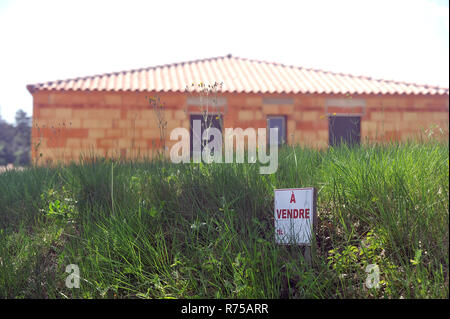 sign indicating that land and house under construction are for sale - Stock Photo