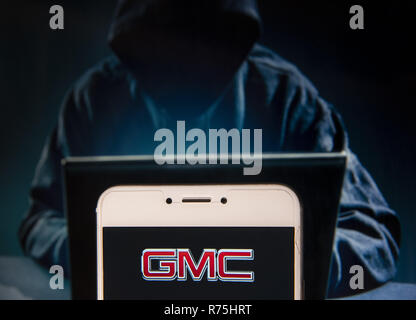 Hong Kong. 23rd Nov, 2018. American automobile manufacturer company General Motors GMC logo is seen on an Android mobile device with a figure of hacker in the background. Credit: Miguel Candela/SOPA Images/ZUMA Wire/Alamy Live News - Stock Photo