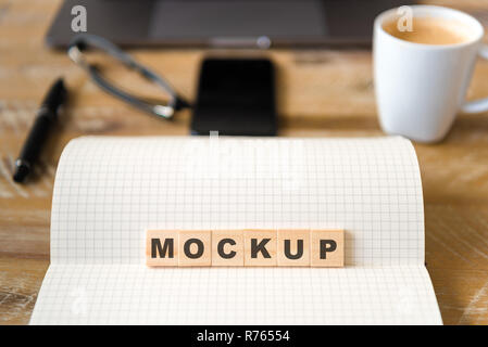 Closeup on notebook over wood table background, focus on wooden blocks with letters making Mockup text - Stock Photo