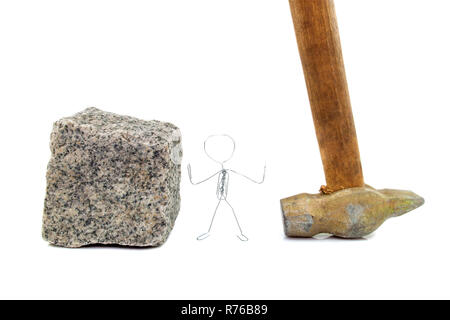 A paperclip figure standing between paving stone and a hammer - Stock Photo