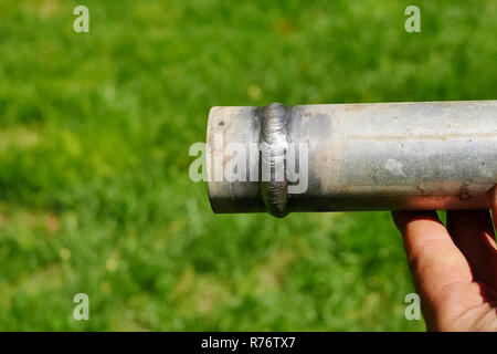 Metal pipe with a welded seam In the hand of a welder's man. - Stock Photo