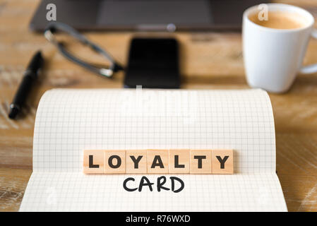 Closeup on notebook over vintage desk background, front focus on wooden blocks with letters making Loyalty Card text - Stock Photo
