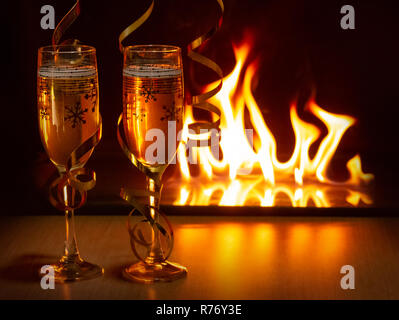 Two glasses of sparkling champagne with golden ribbons against the bokeh background of bright flames creating a cozy atmosphere of Christmas or New Year - Stock Photo