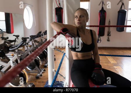 Female boxer relaxing in boxing ring at fitness studio - Stock Photo