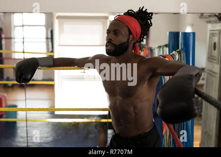 Male boxer relaxing in boxing ring at fitness studio - Stock Photo