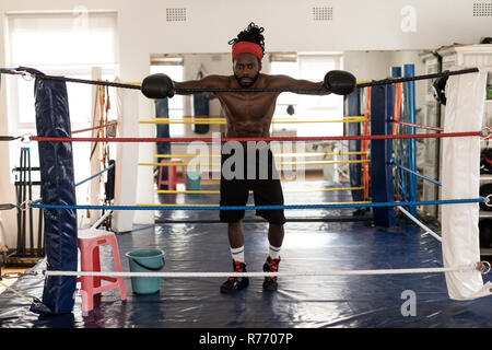 Male boxer standing in boxing ring at fitness studio - Stock Photo