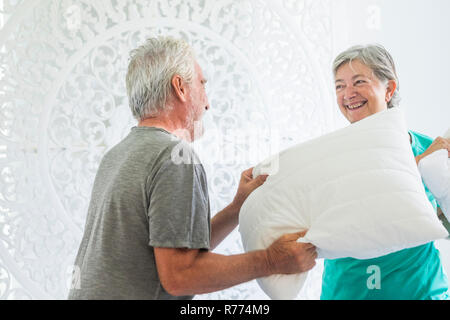 Aged senior adult caucasian couple have fun making war with pillows at home in the bedroom at morning - white bright room and house activity for cheer - Stock Photo