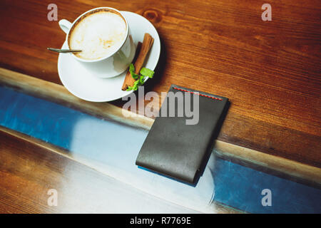 on a wooden table clutch and coffee. - Stock Photo