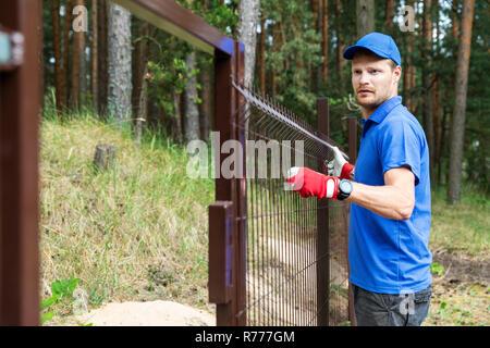 man installing brown metal fence - Stock Photo