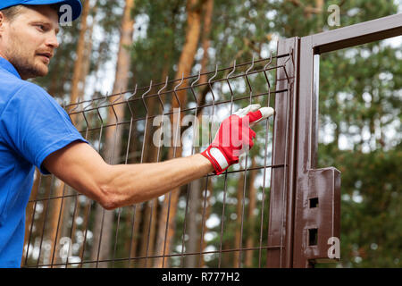 territory enclosure - worker installing metal fence - Stock Photo