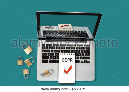 Top view of a laptop, padlocks and a notepad with text GDPR and a ticked checkbox on it - Stock Photo