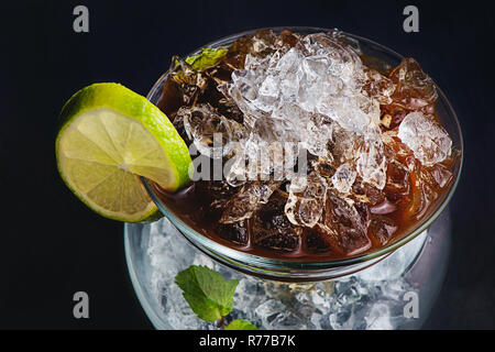 Espresso, mint and lime cocktail in a modern glass bowl. Coffee cold brew concept. Dark background with copy space for a menu. - Stock Photo