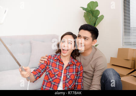 home, people, repair and real estate concept - smiling couple with big cardboard boxes moving to new place and taking smartphone selfie - Stock Photo