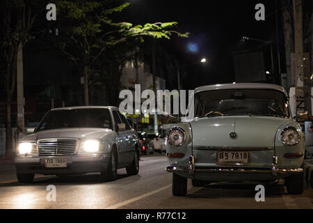 Two vintage and classics cars in the street at night - Stock Photo
