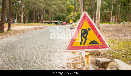 temporary road sign indicating work on a small road in the forest - Stock Photo