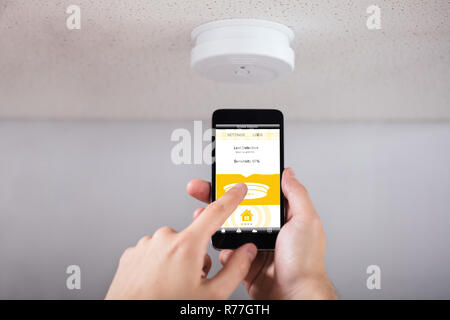 Person Operating Smoke Detector With Mobile Phone - Stock Photo