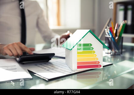 Close-up Of House Model Showing Energy Efficiency Rate - Stock Photo