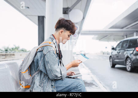 young man is sitting and waiting for bus. He is holding backpack and listening to music from earphones. Guy is looking forward with aspiration - Stock Photo