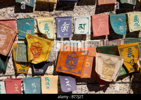 Nepal, Namche Bazar, colourful sun-bleached tourist souvenir Buddhist prayer flags - Stock Photo