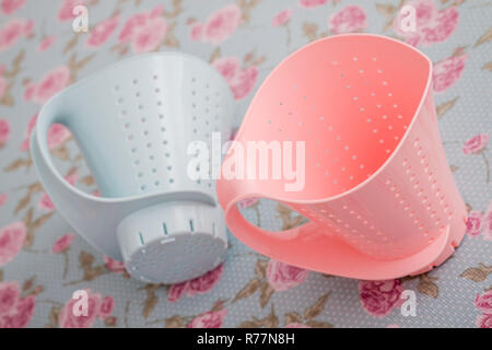 Colorful Plastic Colanders with Handles on Floral Pattern - Stock Photo