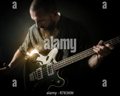 Bearded man playing bass guitar - Stock Photo
