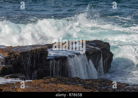 Waves breaking over the rocks at Hermanus, Cape, South Africa. - Stock Photo