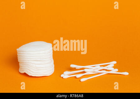 Stack of white round cotton sponge pads and swabs with copyspace on orange background - Stock Photo