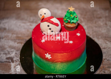Christmas cake decorated with Christmas cupcakes and colorful sweets with Christmas tree - Stock Photo