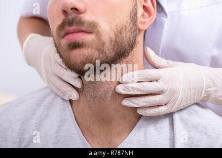 Doctor's Hand Wearing Gloves Performing Physical Exam Palpation Of The Thyroid Gland - Stock Photo