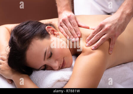 Male Therapist's Hand Giving Shoulder Massage To Relaxed Young Woman - Stock Photo