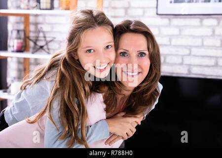 Portrait Of Happy Mature Mother Giving Piggyback To Her Daughter - Stock Photo