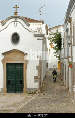 Nossa Senhora da Piedade Church, located along a typical cobbled narrow street inside the old town of Tavira, Algarve, Portugal - Stock Photo