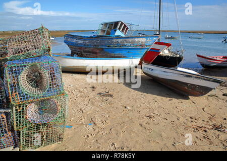 Colorful fishing boats on the beach of Santa Luzia, a fishing harbor located near Tavira, Algarve, Portugal, with fishing baskets in the foreground - Stock Photo