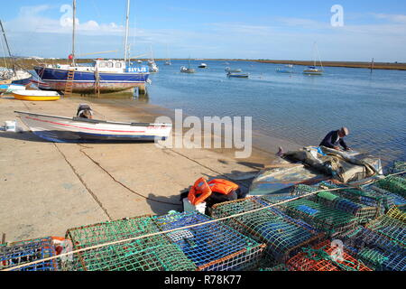 SANTA LUZIA, PORTUGAL - NOVEMBER 19, 2018: The fishing harbor of Santa Luzia, located near Tavira, with a fisherman working on his boat in foreground - Stock Photo