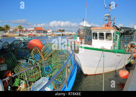 The fishing harbor of Santa Luzia, located near Tavira, Algarve, Portugal, with colorful fishing boats mooring along a jetty and fishing baskets in th - Stock Photo