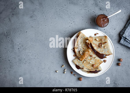 Crepes with chocolate spread and hazelnuts. Homemade thin crepes for breakfast or dessert on grey, copy space. - Stock Photo