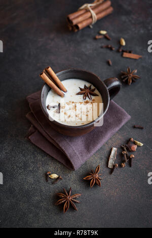 Traditional indian masala chai tea in ceramic cup with ingredients. Spicy black tea with milk (Masala) on rustic dark background. - Stock Photo