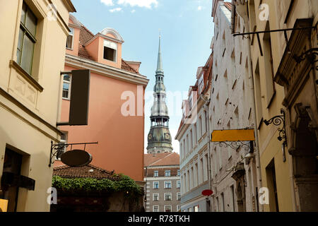 Beautiful small street and church tower in Old Town of Riga, Latvia. City tour, travel - Stock Photo