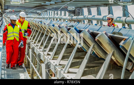 Rustenburg, South Africa, October 15, 2012, Conveyor belt transporting Platinum ore for processing with mining safety inspectors checking for damage - Stock Photo