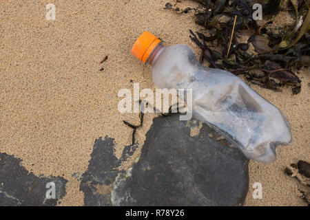 Small plastic water soft drink bottle on a beach - Stock Photo